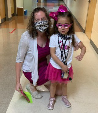 Ms. Wallace and Kindergartner Mackenzie in the school hallway; both are dressed in bright pink and white dresses and wearing masks