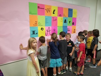 """Our First Graders signing our """"We are Learners"""" wall"""