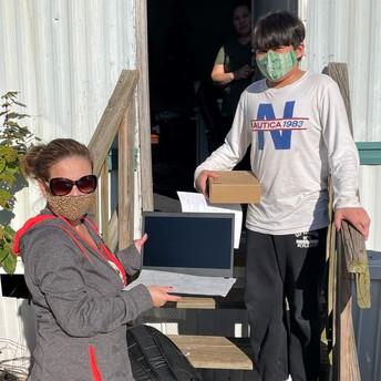 Alichel entregando una computadora portátil a un estudiante