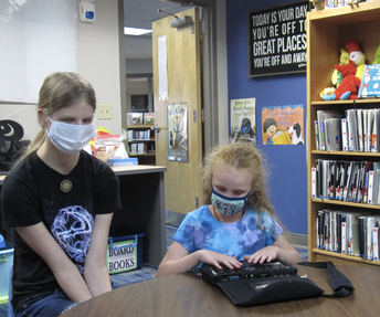 Madison and Maely sit at a table in the library. Maely is exploring her new braille note device.