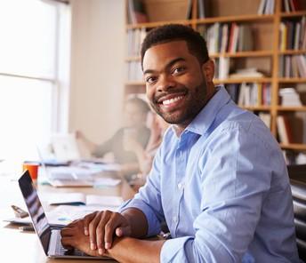 Educator smiling using laptop