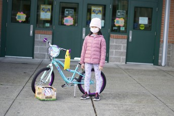 Young girl in face mask with bike