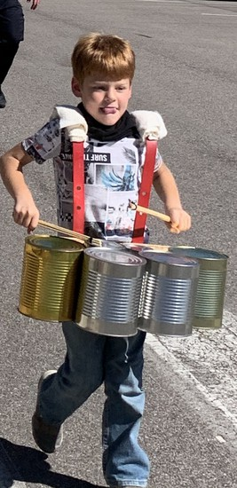 student with a drum made of cans