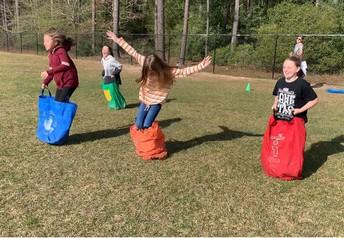 Las estudiantes de quinto grado de PWE disfrutan de carreras de sacos durante el día de campo.