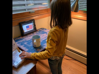 Greta standing for the Pledge of Allegiance at the beginning of her distance learning day!