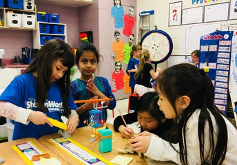 Grade 2 students work to problem-solve a Rube Goldberg machine