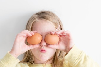 photo of girl holding two eggs