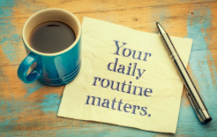 Coffee cup on a wooden table, a pen and a napkin that says Your daily routine matters.