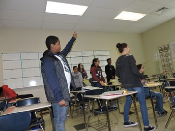 Students standing in class, one with hand raised