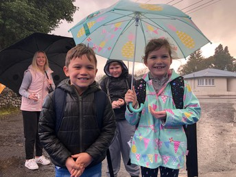 Sharing the umbrella on a wet walk to school! Manaaki tangata!
