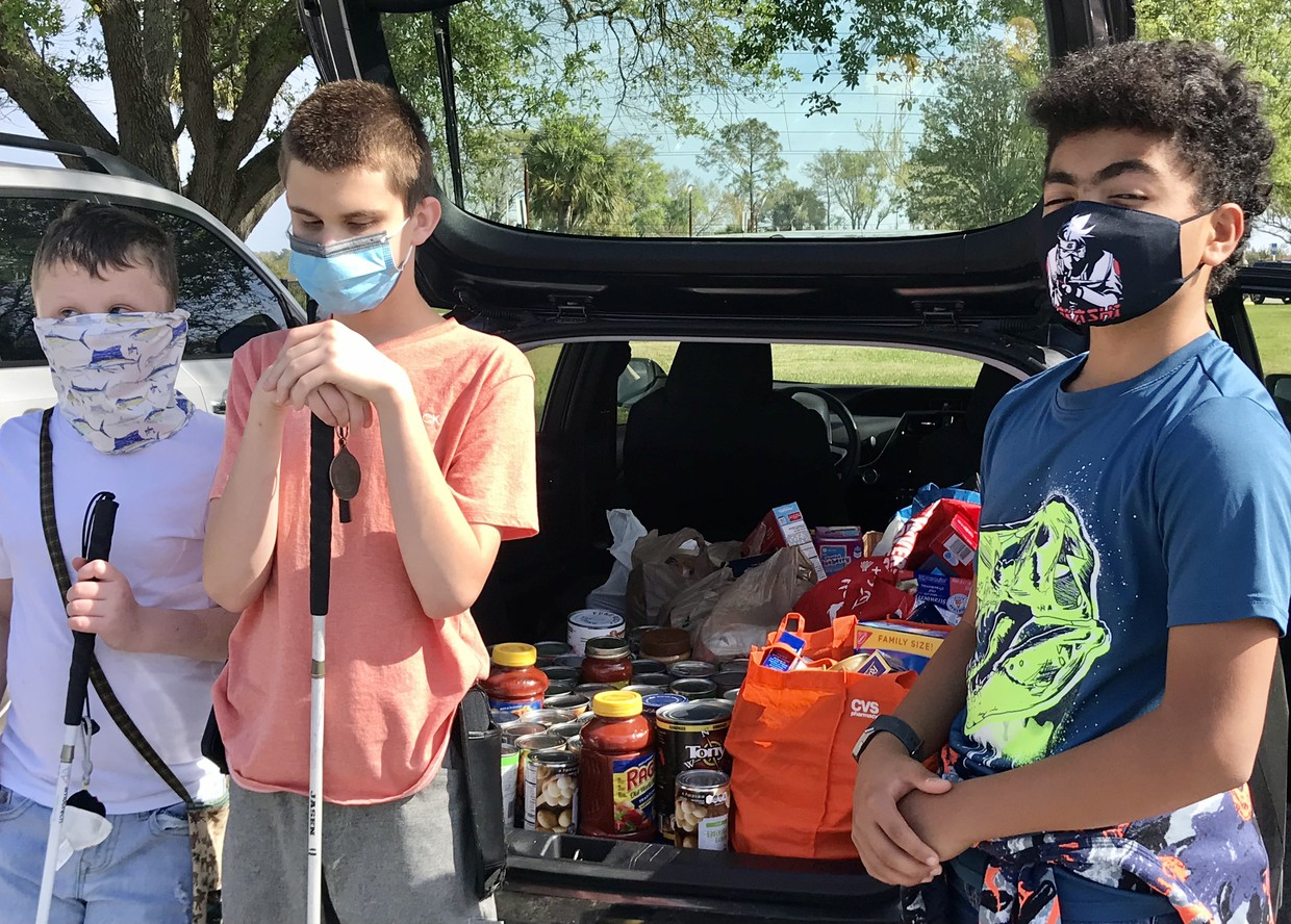 3 masked students stand at the back of a car with the trunk open; inside are cans, boxes, and bags of food covering the entire floor of the trunk