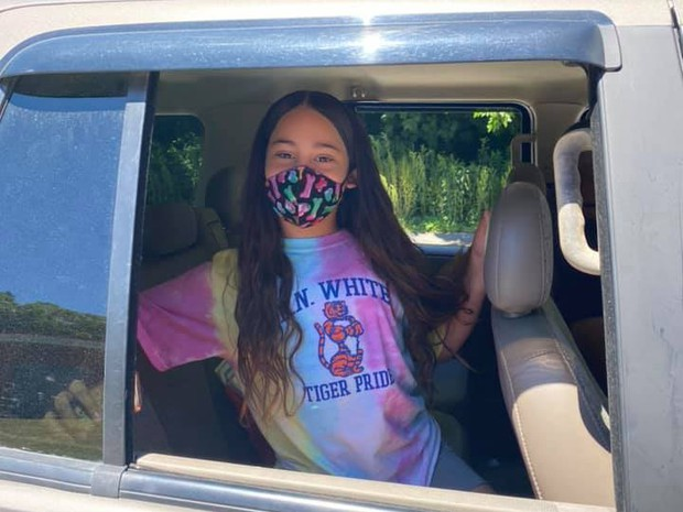 Student wearing her mask at a 5th grade drive thru graduation ceremony.