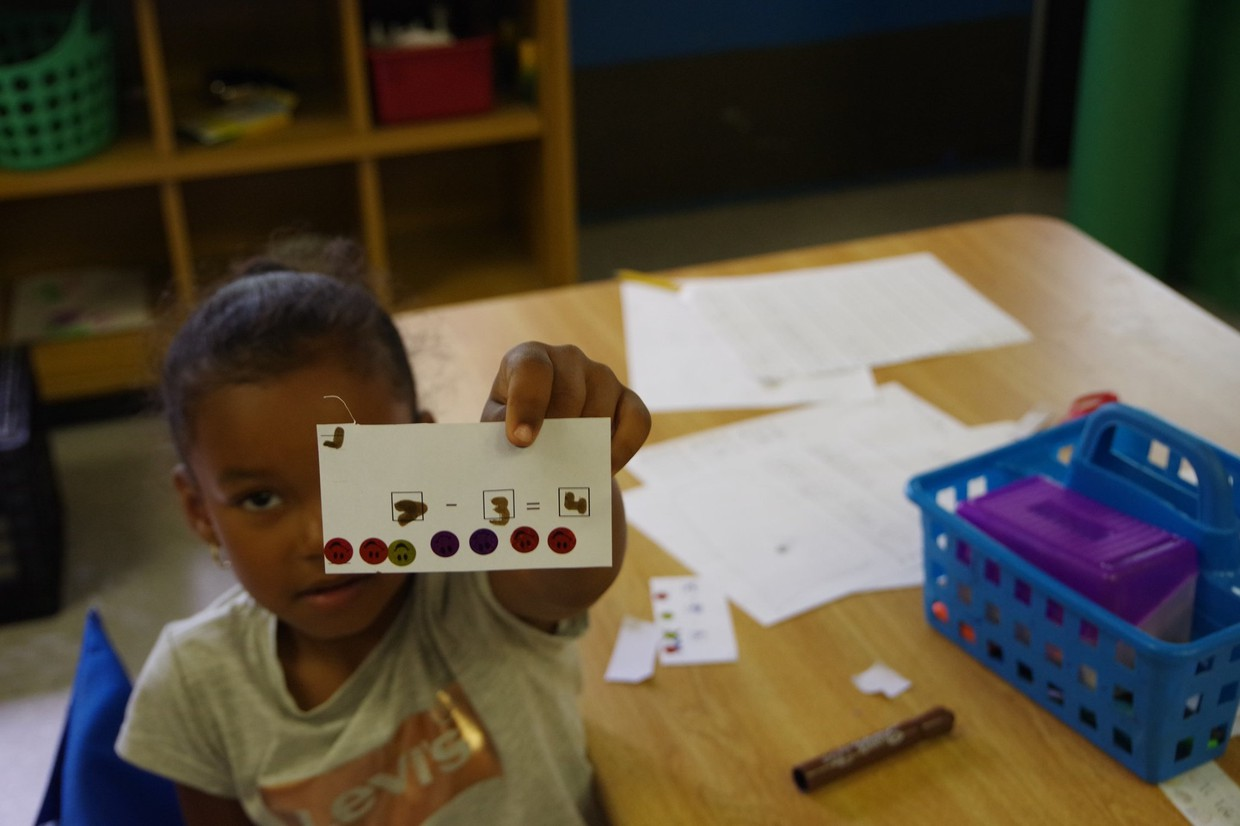 Kelly School student holds math subtraction flash card