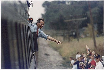 Color Photo: President Bush 41 waves from the back of the train outside of Bowling Green as he travels on a whistle-stop campaign through Ohio in 1992