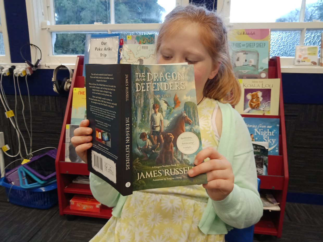 Kaitlin from Room 7 reading her new Dragon Defenders book which arrived this morning!
