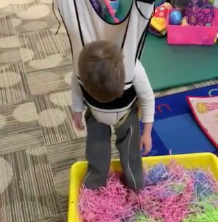 student stands with feet in a sensory bin