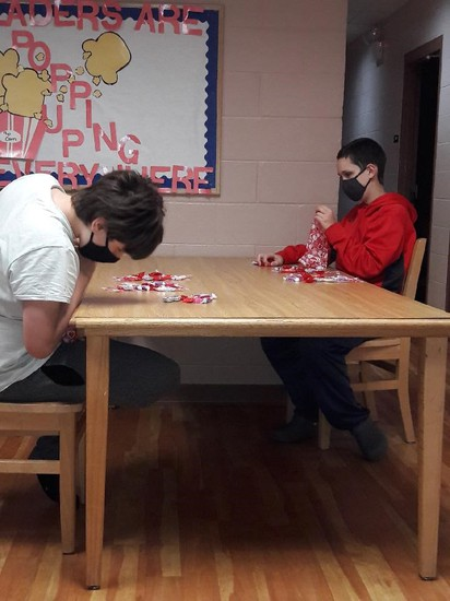 2 students sitting a table; on the table are heart cellophane bags and lots of candy