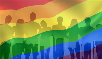 Outline of people standing together behind a rainbow flag.