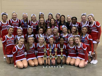 Hewitt-Trussville Middle School cheer team kneeling as a group with four large trophies front and center