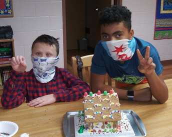 Two students sitting at a table behind their gingerbread house creation