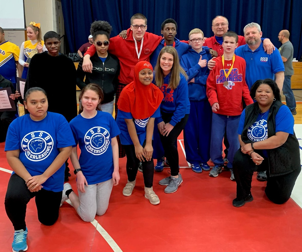 OSSB wrestlers, coaches and cheerleaders pose during a recent meet. Back row L to R are Elliott, Kurtacee, Carl, Marwan, Ian, Coach Heath, Evan, and Coach Mascarello. Shown in front are Lalita, Autum, Sumeya, Coach Traucht, and Coach Knight.