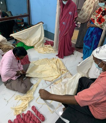 Tearing strips of silk from the saris to make ribbons