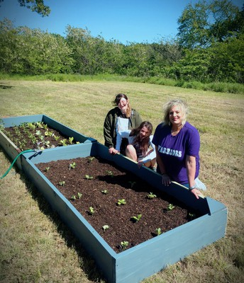 Maggie, Carrie, and Ms. Kelton are all smiles after completing their garden!