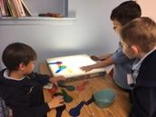 Kindergarten students collaborating on designs