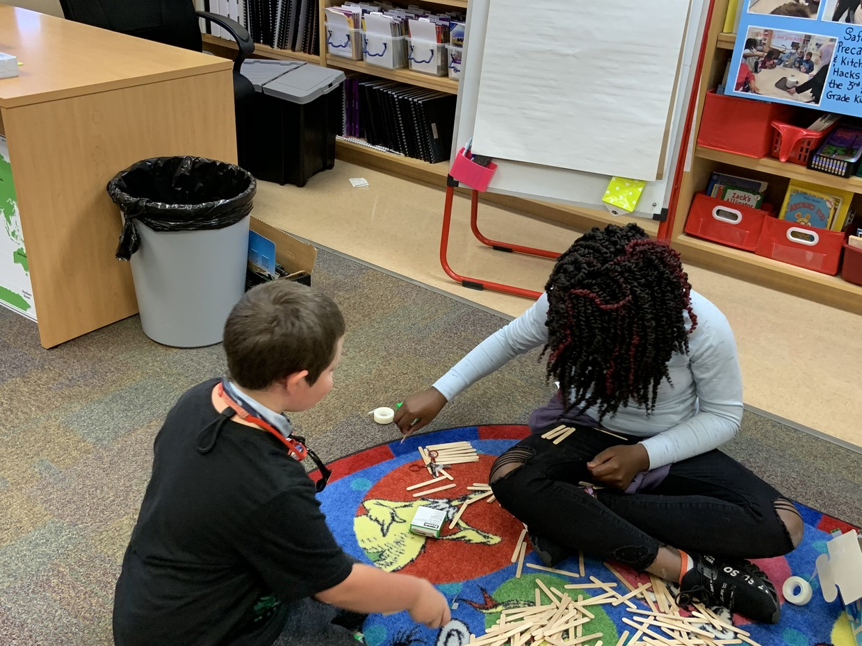 Two students are sitting on the floor of a classroom with many popsicle sticks and some tape and rubber bands strewn around.