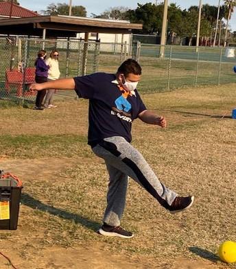 Student balances himself after kicking the yellow kickball