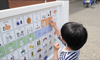 Student pointing at a grid icon on new alternative communication board on playground at Paine Elementary School