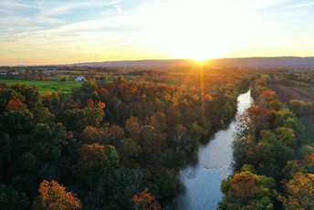 Image shows a sunrise over trees and a river.