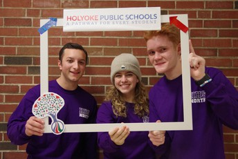 Two male and one female HHS student posing with a photo booth frame