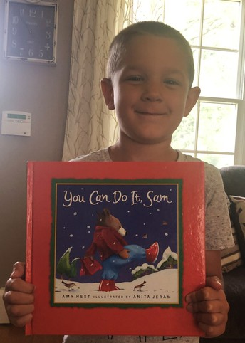 kindergarten student holds You Can Do It Sam book