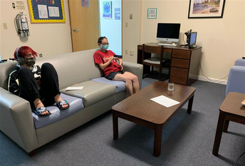 2 students relax on a couch; both are wearing masks and spaced apart. A coffee table, end table, and desk with computer are in the room with a bulletin board and open door leading to hallway