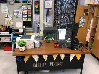 Sneeze guards around teachers' desks.