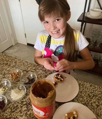 Madeline decorating her apple cookies