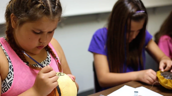 Native American students painting and sewing authentic crafts