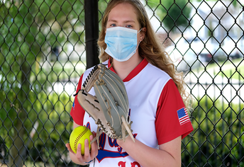 Female athlete in softball uniform and face mask