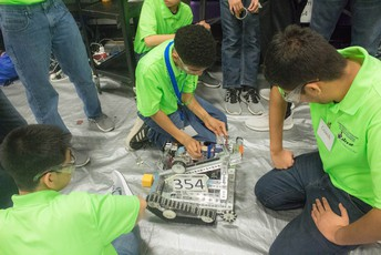 Image of a robotics team working on their robot.