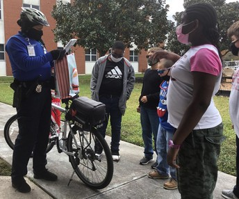 Officer Anderson standing next to her bike, peering into the Christmas gift bag with students surrounding her