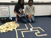 Fifth graders build their maze as they program their robot