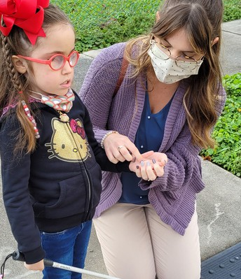 A young student holding her cane is standing on a warning track on sidewalk; her teacher is kneeling beside her