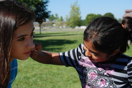 A WLHS member with a child painting an image on her cheek.