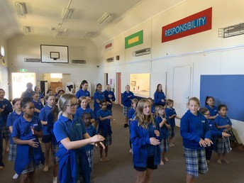 Madison, Brooklyn, and Beth teaching the girls actions for the waiata.