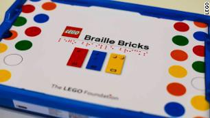 Picture shows a white box with colorful dots from the LEGO Foundation. Words appear in print saying LEGO Braille Bricks. Underneath the words are the same characters shown in braille.