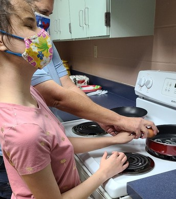 Student being assisted in breaking an egg on the side of a pan on the stove