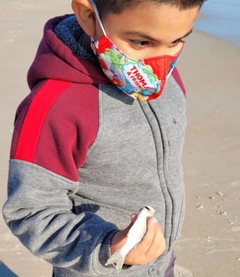 Jayden, wearing a hoodie and mask, is standing on the beach; in his right hand is a white fish about 4 inches long