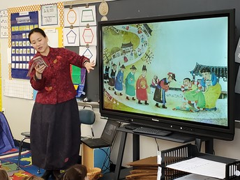 """Mrs. Heo is reading the Korean """"Cinderella"""" to the class."""