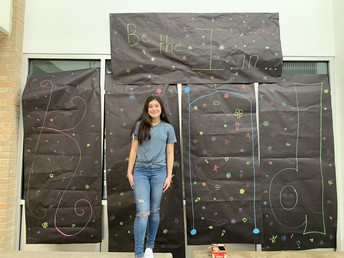 """image of student in front of banner reading """"be the I in KIND"""""""